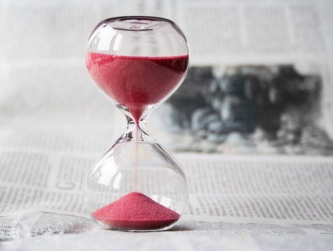 An hourglass with pink sand sitting on a newspaper