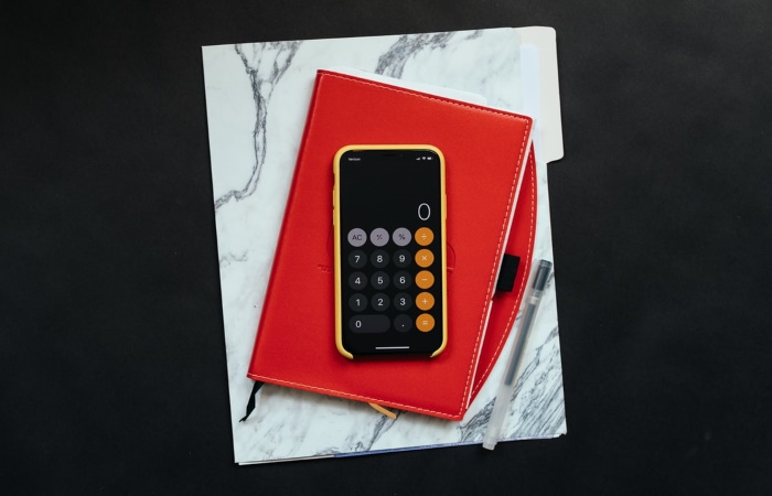 Calculator app on iPhone on top of a red organiser and marble folder