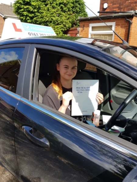 Jessica in her learner car with her pass certificate
