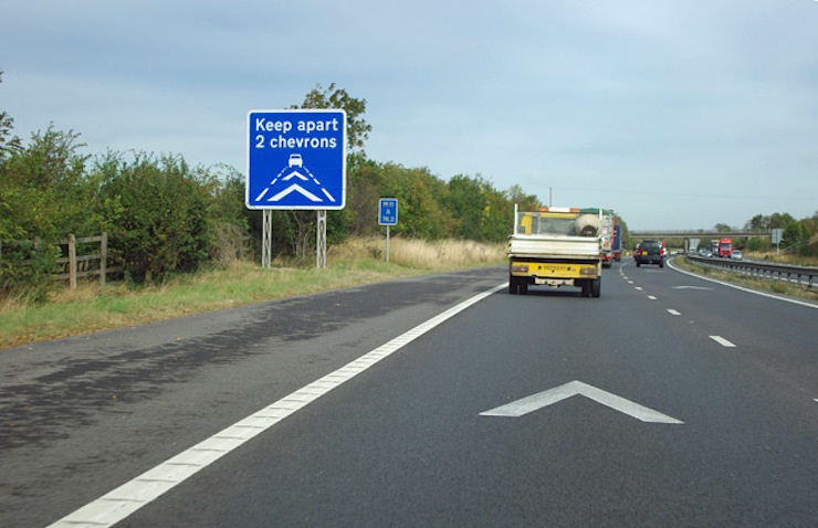 A road sign warning drivers to keep two chevrons apart on motorway