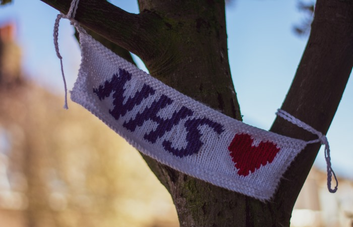 A knitted NHS flag hanging on a tree