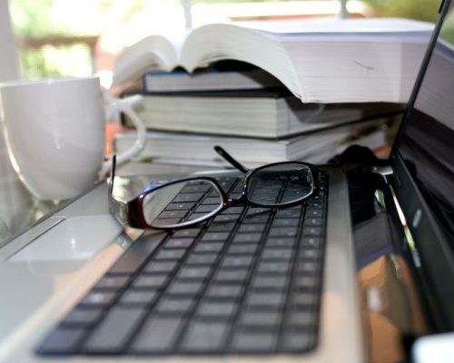 Laptop with books and reading glasses