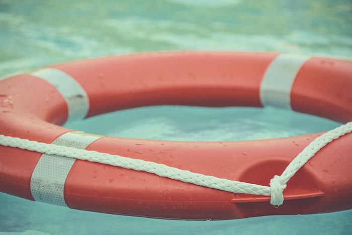 Red and white lifebuoy floating in water