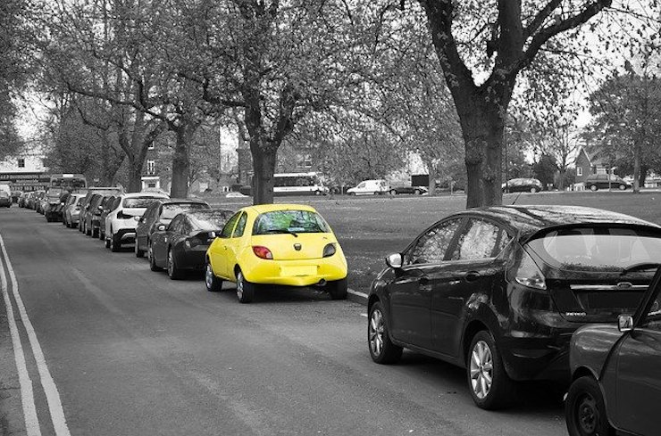 One yellow car amongst a line of parked cars