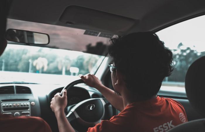 Man wearing red shirt driving