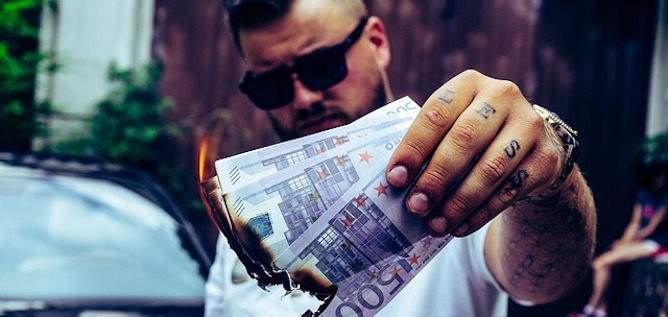 A man in sunglasses burning money in front of a car