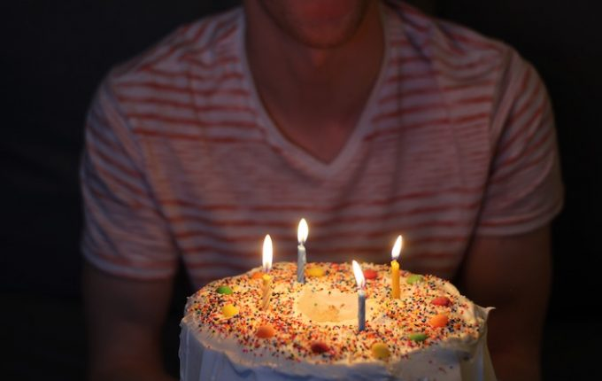 A man carrying a birthday cake with lit candles