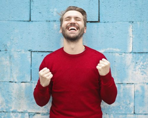 Man in red jumper pumping fists and smiling in celebration