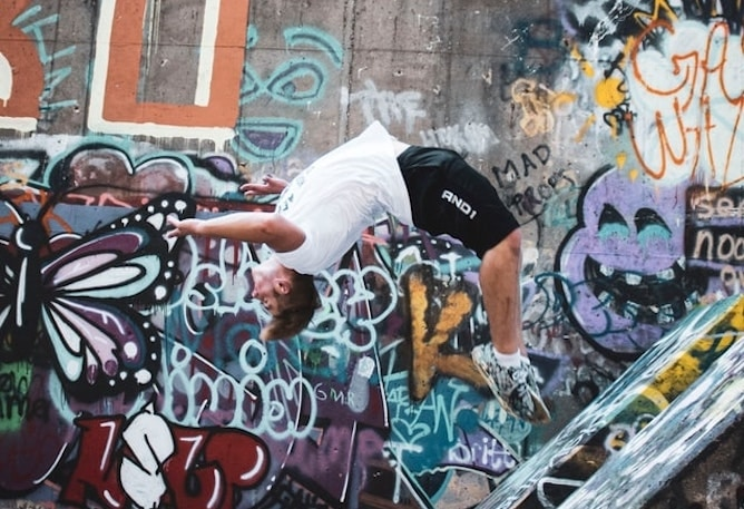 A man doing a backflip with a graffitied wall in the background