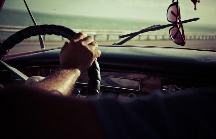 Man driving near coast with sunglasses hanging near windscreen