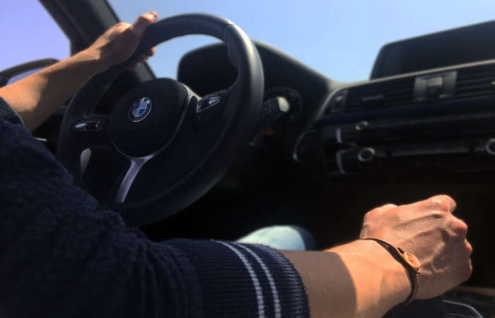 Man holding steering wheel and gear stick