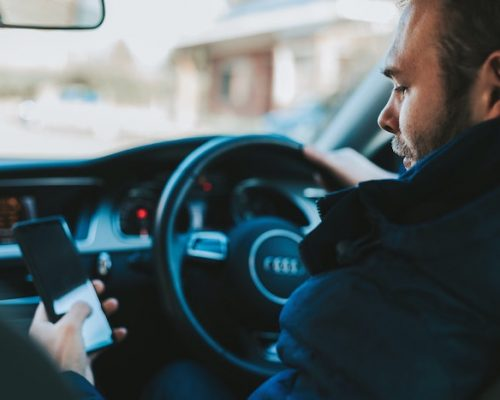 A distracted driver: a man sitting in the driver's seat, with one hand on the steering wheel, looking at his phone, held in his other hand