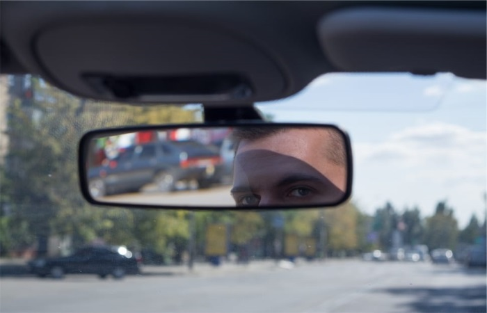 A woman adjusting her internal car mirror