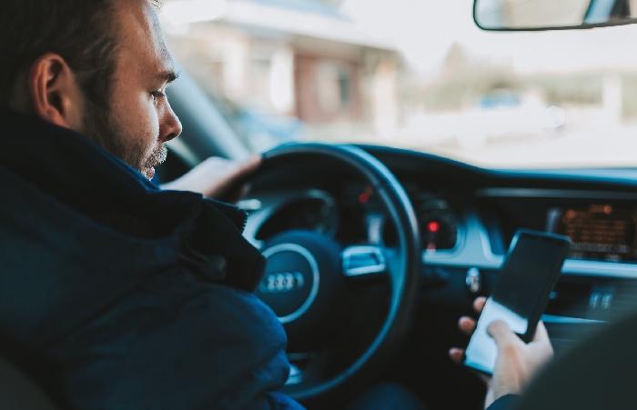 Man sat in driver seat of car looking at phone