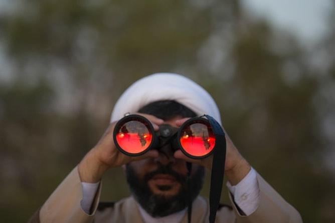 A man watching the sunset through binoculars