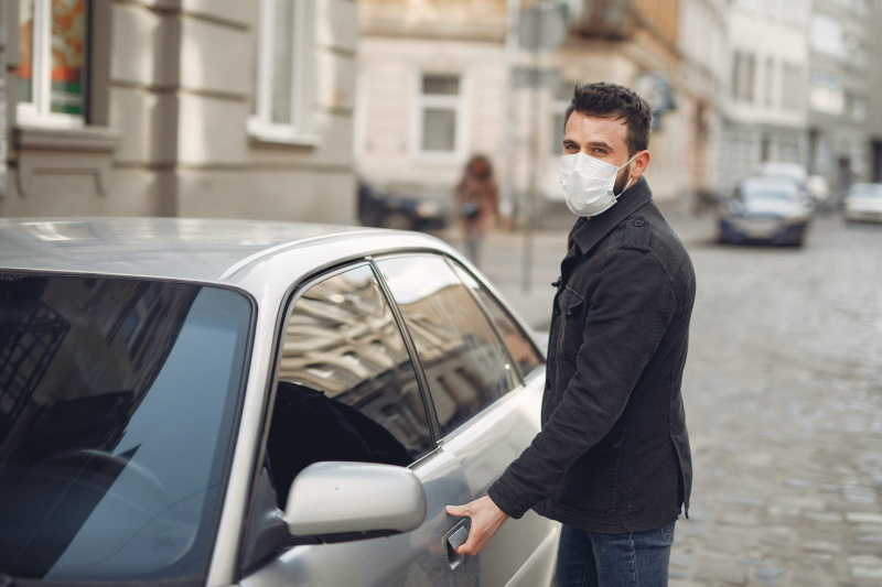Man wearing face mask opening car door