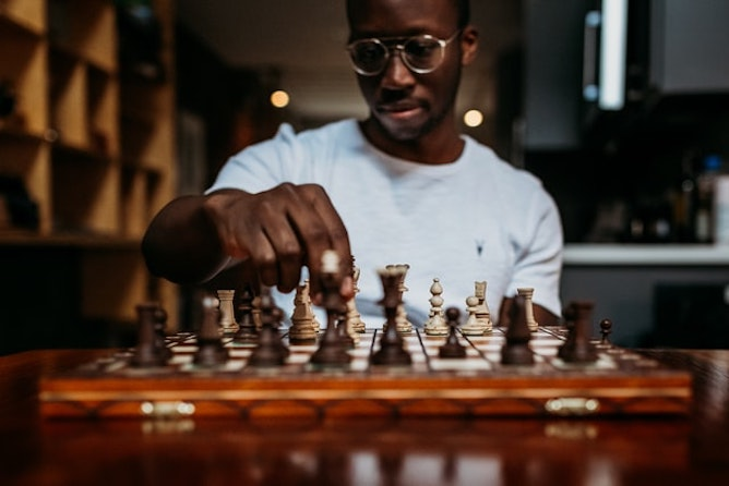 A man in a white tshirt with glasses playing chess