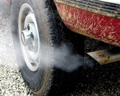 Exhaust fumes from a muddy red car