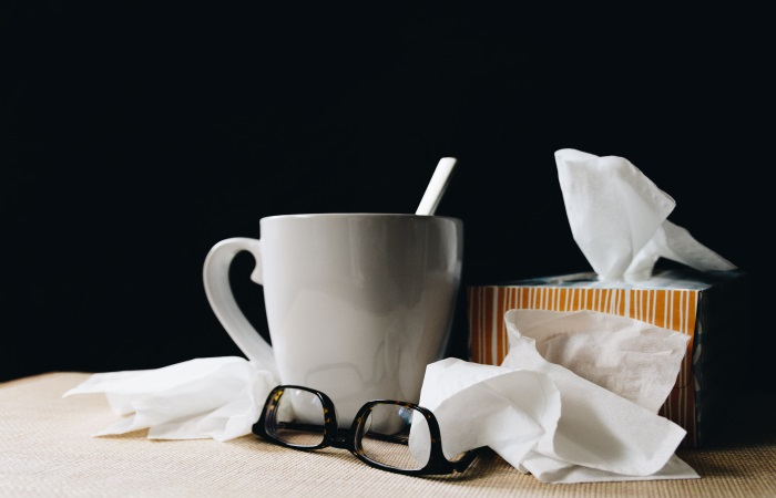 A mug with a box of tissues and pair of glasses