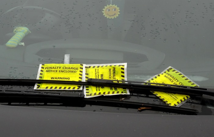A traffic warden giving a parking ticket