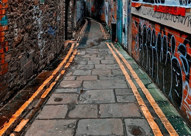 A narrow alleyway with graffiti on the walls and double yellow lines
