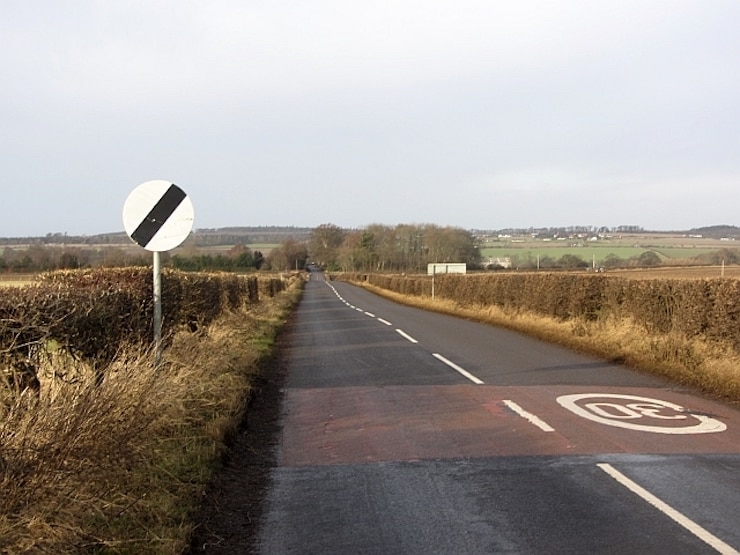 The UK national speed limit sign on a country road