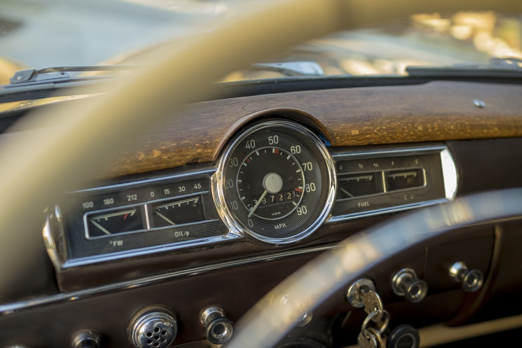 Dashboard of old car with speedometer in the middle.