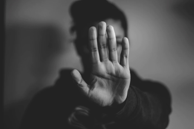 A greyscale photo of a person whose face is covered by their outstretched palm