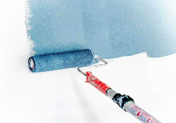 Paint roller painting white wall blue