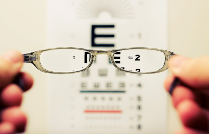 Pair of glasses held up to eyesight test