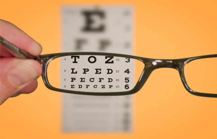 Someone holding glasses looking at eyesight test