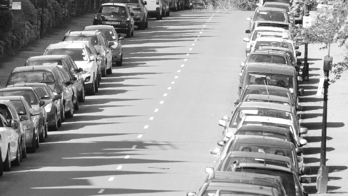 Black and white image of road with lines of parked cars on either side
