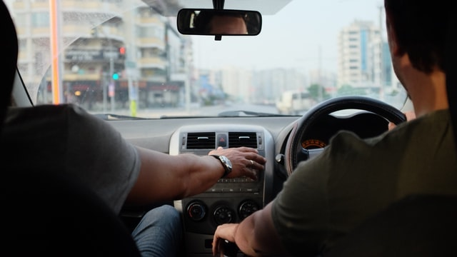 A man driving while the passenger reaches for the steering wheel