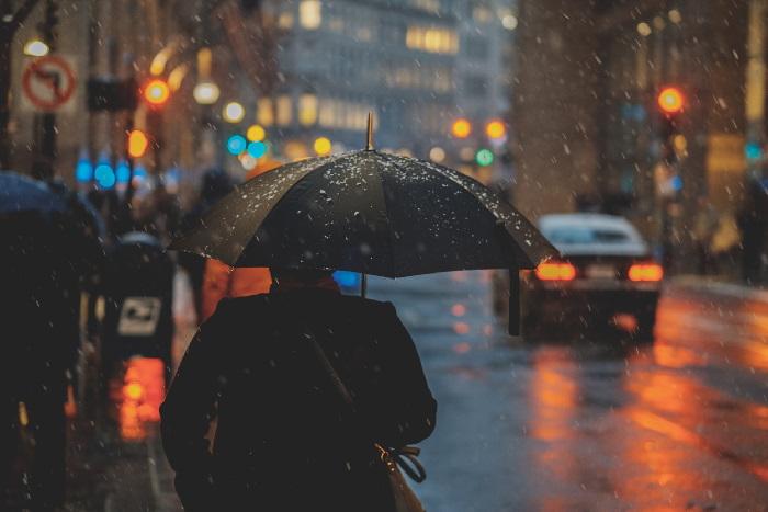 Pedestrian holding black umbrella next to road