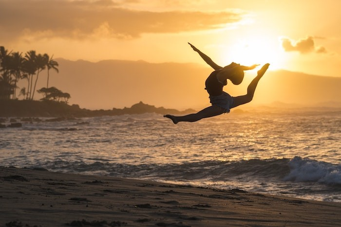 Person doing jump splits on the beach at sunrise
