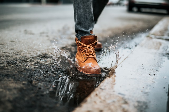 A person wearing a brown boot stepping in a puddle beside the kerb