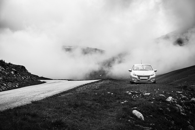 A Peugeot 208 up a mountain with fog in the background