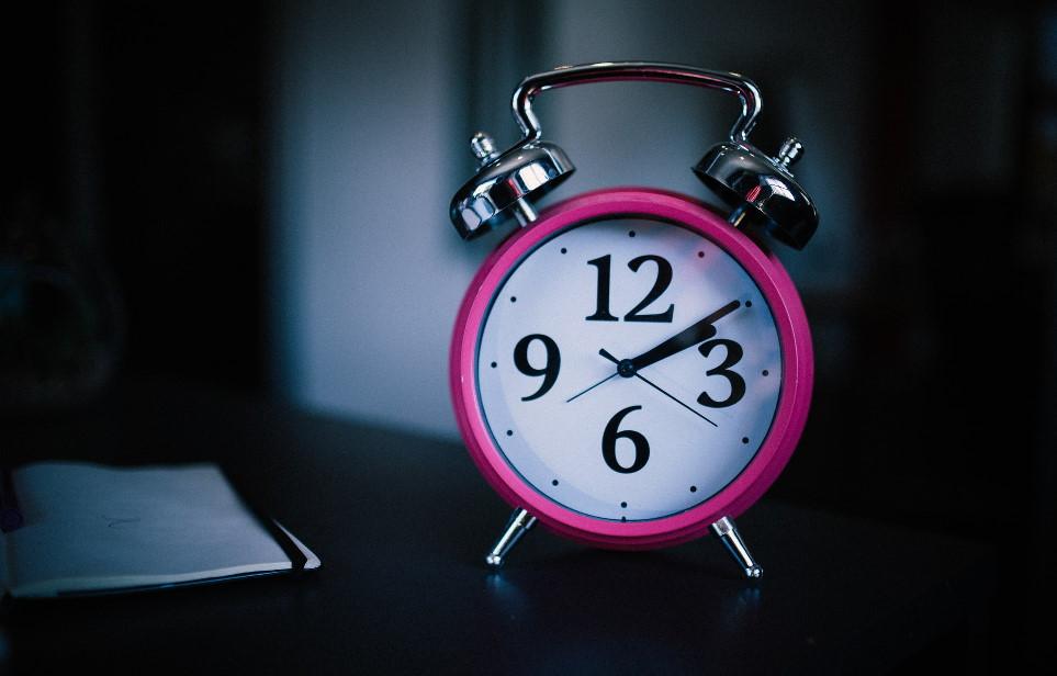 Pink alarm clock on dark table