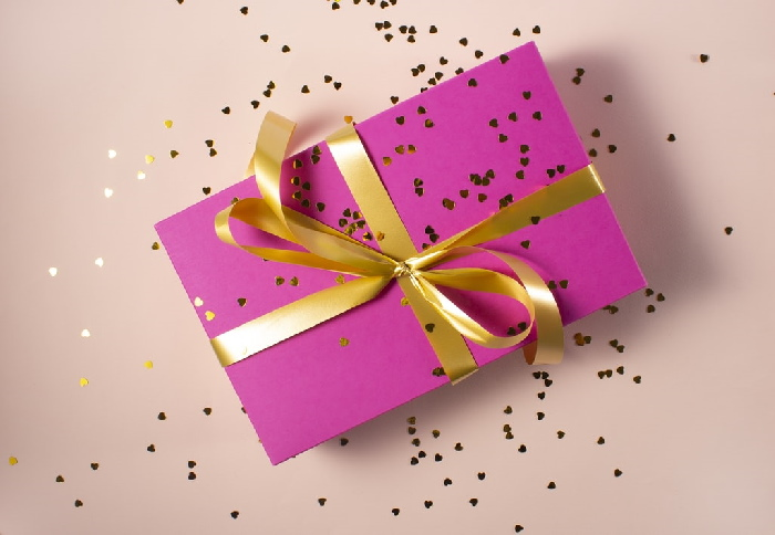 A present wrapped in pink paper and a gold bow with glitter.
