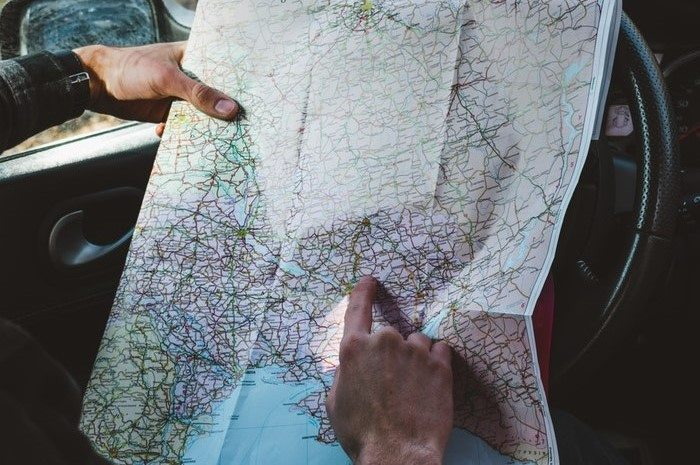 Man in car pointing at location on a map