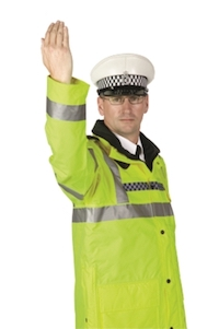 A police officer standing side on beckoning traffic on from the side