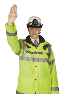 A police officer facing the camera and holding up their right hand to signal to oncoming traffic that they must stop