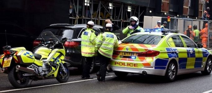 Police officers surrounding a vehicle