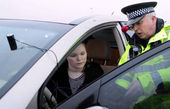 Policeman talking to a young woman in her car