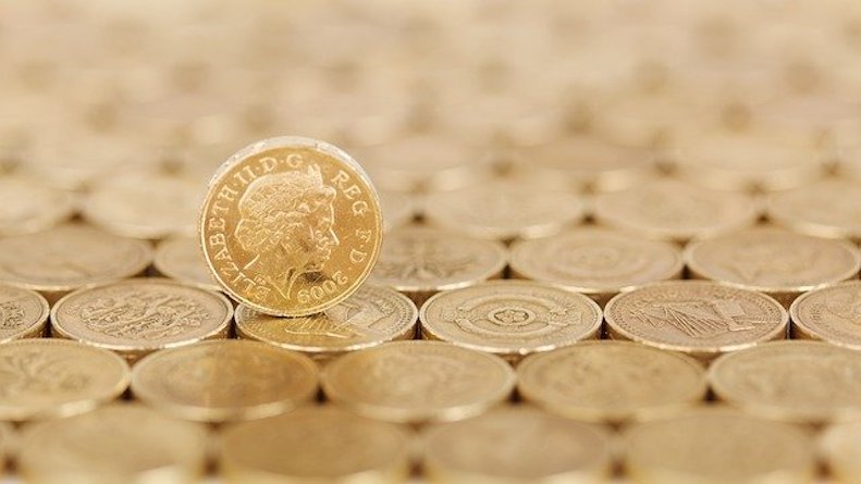Rows of pound coins with one standing up