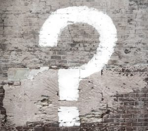 White question mark painted on brick wall