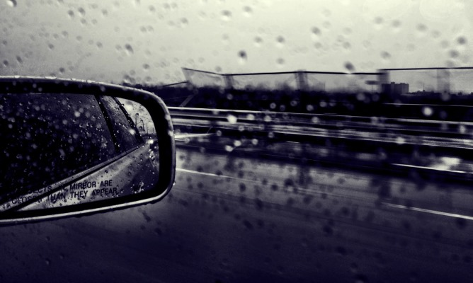 Raindrops on car window and side mirror