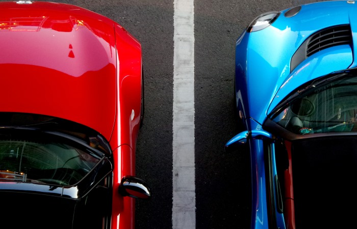 Red and blue cars parked in bays next to each other