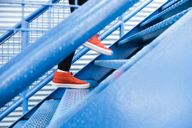 Person wearing red shoes walking up a flight of blue stairs