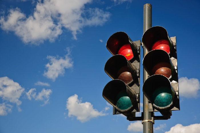 Traffic lights on red against blue sky with clouds